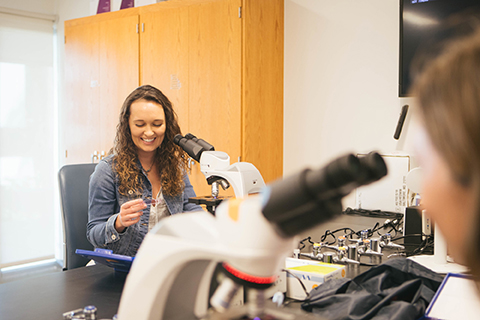 Student smiling at microscope